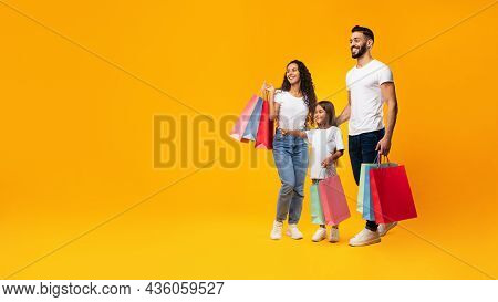 Happy Arab Family Shopping Holding Shopper Bags, Yellow Background, Panorama