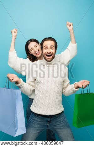Astonished Man Holding Shopping Bags Near Woman Showing Yeah Gesture Isolated On Blue
