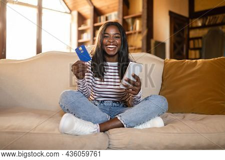 Young Black Lady With Cellphone And Credit Card Buying Goods In Online Store, Using Mobile Banking A
