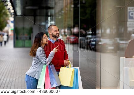 Portrait Of Smiling Young Inrerracial Couple Holding Shopper Bags, Pointing At Shop Window, Walking