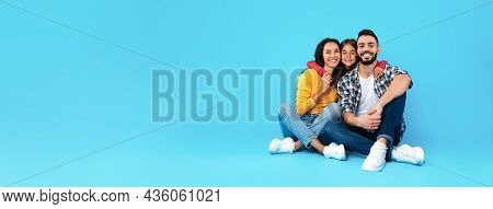Middle-eastern Parents And Daughter Embracing Near Empty Space, Blue Background