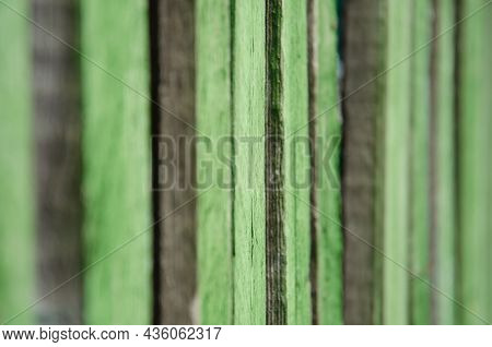 Close-up Old Green Wooden Fence With Copy Space. Wall Of Frayed Wooden Planks. Texture Of Old Wooden