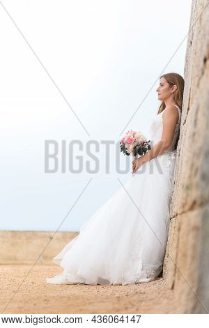 Brunette Bride In White Dress Leaning On A Wall Looking Out To Sea