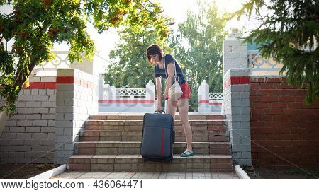 Woman With A Heavy Suitcase Hardly Climbs The Stairs Of The Railway Station.