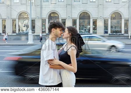 Young Guy With A Girl Hugging In The Summer In The City. The Roadway With Blurred Moving Cars Is Vis