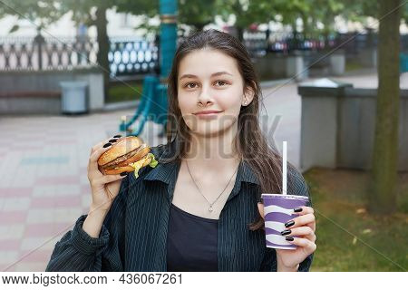 Young Brunette With A Smile Holds A Cheeseburger And A Glass With A Drink In Her Hands.