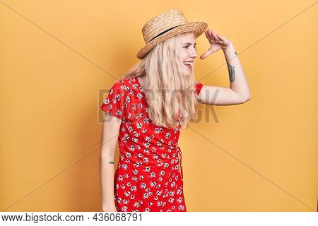 Beautiful caucasian woman with blond hair wearing summer hat very happy and smiling looking far away with hand over head. searching concept.