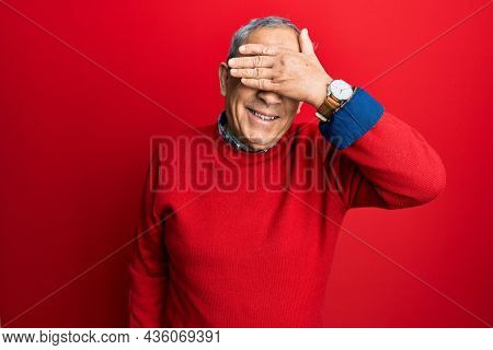 Handsome senior man with grey hair wearing casual clothes and glasses smiling and laughing with hand on face covering eyes for surprise. blind concept.