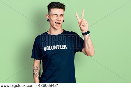 Young caucasian boy with ears dilation wearing volunteer t shirt smiling with happy face winking at the camera doing victory sign with fingers. number two.