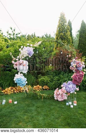 Stylish Wedding Arch Decorated Fresh Flowers And Candles In The Beautiful Landscaping Garden Among L