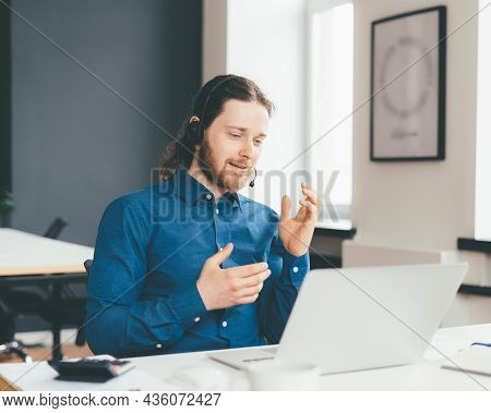 Smiling Young Man Operator In Headset And Casual Wear Talking With Client On Laptop In Office. Moder