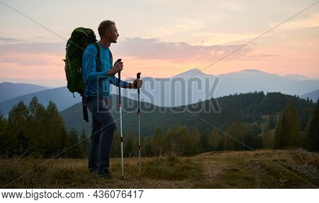 Man Traveler Against Backdrop Of Mountain Hills And Pink Cloudy Evening Sky At Sunset. Hiker With Tr