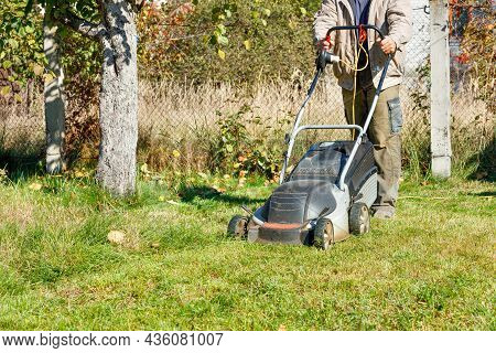 A Gardener Tends A Green Grass Lawn And Mows Grass With An Electric Lawn Mower On His Backyard On A