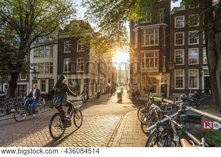 Amsterdam, Netherlands - September 22, 2021: Early morning in Amsterdam. People ride bicycles, the ancient European city of Amsterdam. Sunlight and silhouettes, beautiful downtown