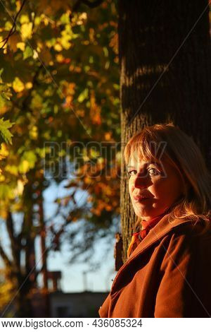 Portrait Of Elegance Caucasian Blonde Woman In Colorful Yellow Maple Autumn Park. Bright Stylish Wom