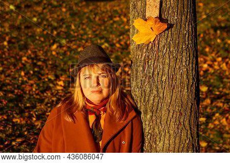 Portrait Of Pretty Caucasian Blonde Woman In Colorful Orange Autumn Park. Bright Stylish Woman In Ha