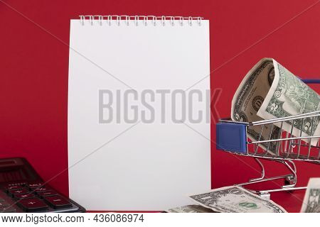 White Notepad With Calculator And Stylish Pen On A Red Background. Copy Space.