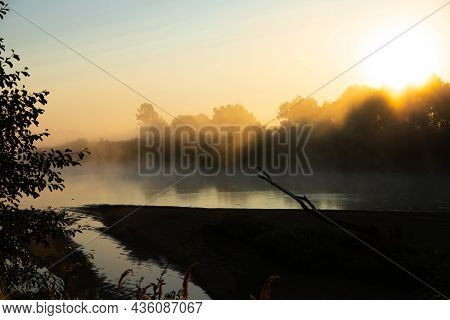 Foggy Morning On A European River With Fresh Green Grass In The Sun. The Rays Of The Sun Through The