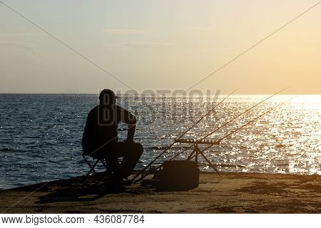 A Fisherman Is Fishing With Afishing Rod On The Seashore, Opposite The Sun. High Quality Photo