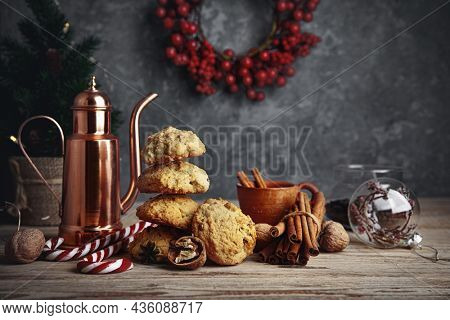 Homemade cookies with cup coffee nuts and copper coffeepot on old wooden board in rustic style. Still life with festive treats.
