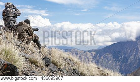 Ibex Hunters Are Searching For Animals With Optics And Binoculars. Two Men In Camouflage Clothes In