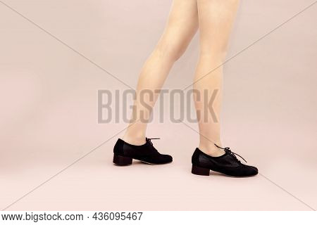 Black Suede Lace Up Shoes And Woman's Caucasian Legs On Light Powdery Pink Background. English Brogu