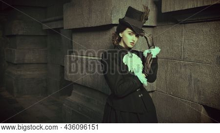 Vintage portrait of a pretty confident young lady of the 19th century posing late in the evening on a city street. Style of the late 19th - early 20th century. Copy space.