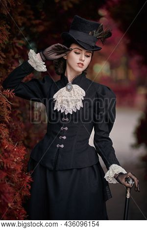 Historical reconstruction of the late 19th and early 20th centuries. Elegant brunette lady in a strict black dress posing in an autumn park. Historical makeup and hairstyle.
