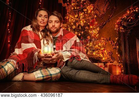 Cozy Christmas evening. Christmas celebration. Romantic couple of young people in love wrapped in a warm blanket spend evening by a xmas tree.