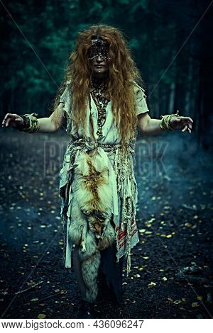 Woman shaman. Full length portrait of a frightening forest witch with a mask on her eyes doing her mystical ritual in a magic forest at night. Paganism. Death ritual. Halloween.
