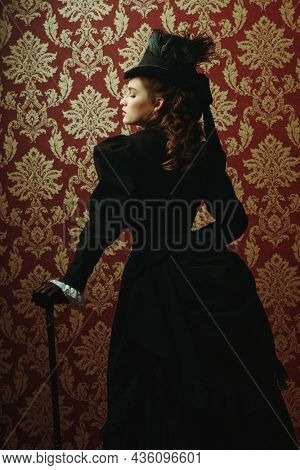 19th century fashion and beauty. Beautiful young lady in an elegant black 19th century suit and hat posing on a vintage background with a walking stick in her hand.
