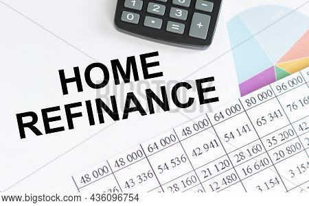 Home Refinance Text On White Paper On A Desktop With Calculator And Financial Charts. Business And F