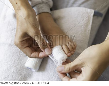 Mother Bandages Her Childs Big Toe. Close-up Photo Of Kids Foot With Bandaged Finger. First Aid In C