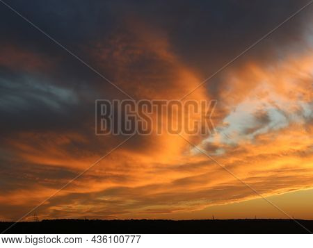 Orange-gray Thunderclouds In The Sunset Sky Over A Dark Strip Of Forest, Dramatic Landscape With A L