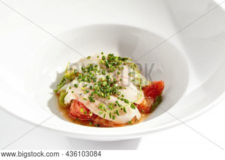 Healthy dinner - fish fillet with tomato and avocado on white plate. Diet food - cooked seabass on vegetables garnish. Keto diet in restaurant menu. Fish menu - cod, snapper, whitefish, catfish