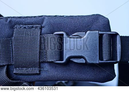 One Closed Black Plastic Latch On The Harness Of The Backpack On A White Background