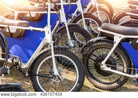 Many Retro Fat Electric Bicycle Scooters Parked On Dirt Grass Field Outdoor Ready For Hire Rental Sh
