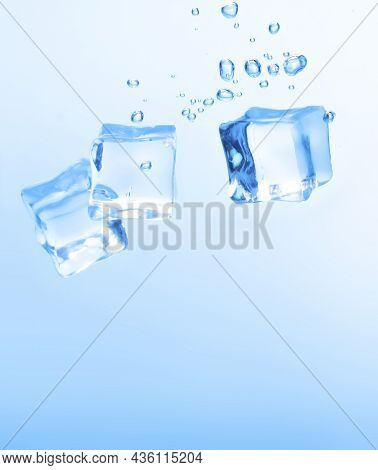 Ice Cubes In Blue Water Create Bubbles That Float To The Surface, Blue Liquid.