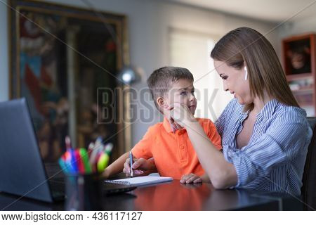 Young Caucasian Mom Playing With Son During Online Job At Home Office