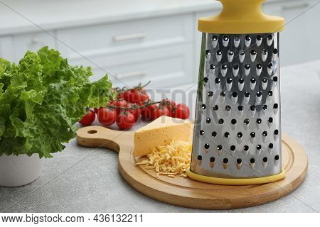 Grater, Cheese And Vegetables On Table In Kitchen
