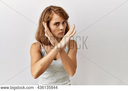 Beautiful caucasian woman standing over isolated background rejection expression crossing arms doing negative sign, angry face