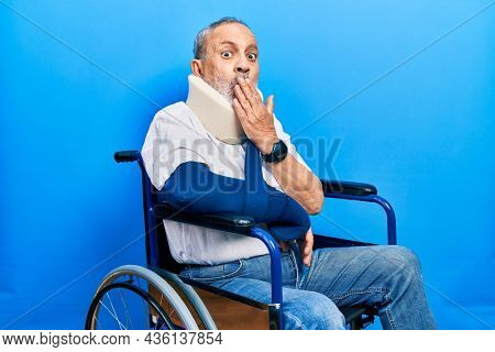 Handsome senior man with beard sitting on wheelchair with neck collar an arm sling covering mouth with hand, shocked and afraid for mistake. surprised expression