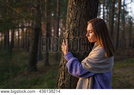 Loving Nature Purity: Relaxed Woman Embracing Tree Trunk In Autumn Forest With Closed Eyes At Sunset