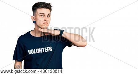 Young caucasian boy with ears dilation wearing volunteer t shirt cutting throat with hand as knife, threaten aggression with furious violence