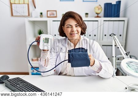 Middle age hispanic doctor woman using blood pressure monitor winking looking at the camera with sexy expression, cheerful and happy face.