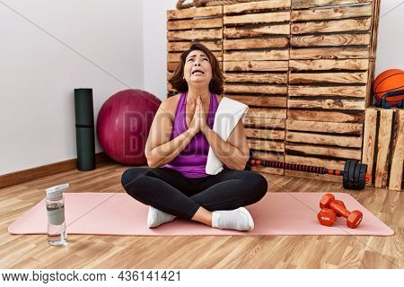 Middle age hispanic woman sitting on training mat at the gym begging and praying with hands together with hope expression on face very emotional and worried. begging.