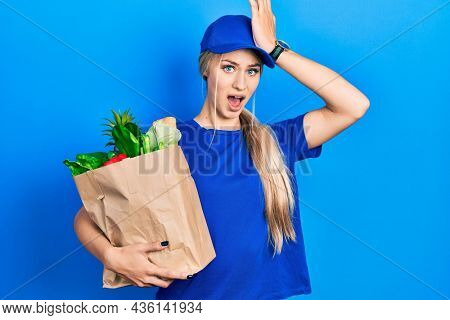 Young caucasian woman wearing courier uniform with groceries from supermarket surprised with hand on head for mistake, remember error. forgot, bad memory concept.