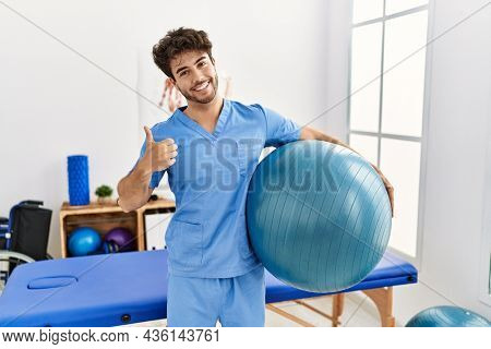 Hispanic physiotherapy man working at pain recovery clinic smiling happy and positive, thumb up doing excellent and approval sign