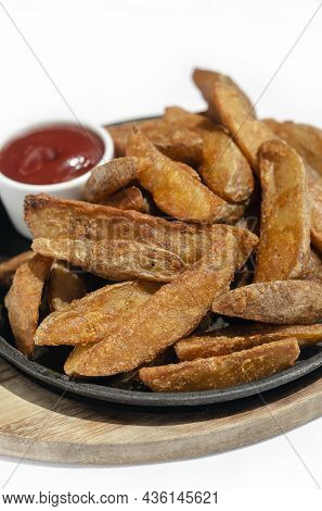 Spicy Curry Powder Coated Crispy Deep Fried Potato Wedges On Plate With White Background