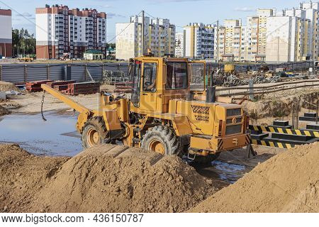 Powerful Wheel Loader For Transporting Bulky Goods At The Construction Site Of A Modern Residential